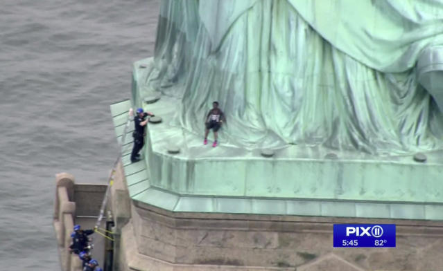 In this image made from video by PIX11, a person, center, leans against the robes of the Statue of Liberty on Liberty Island in New York, as one of the police officers climbed up on a ladder to stand on a ledge nearby talking the climber into descending on Wednesday, July 4, 2018. Shortly before the climber scaled the statue's base, forcing its evacuation, several people who hung a banner from the Statue of Liberty's pedestal calling for abolishing the federal government's chief immigration enforcement agency were arrested. (PIX11 via AP)