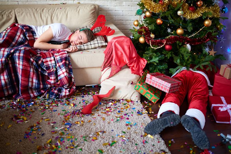 Young man in reindeer antlers napping on sofa, Santa Claus sleeping under Christmas tree