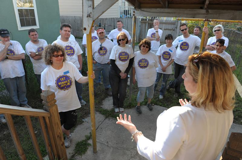 Nearly two dozen volunteers from Rebuild Joplin who traveled from Joplin, Mo. to work with The St. Bernard Project listen to Kelly Schultz, with the New Orleans Tourism and Marketing Bureau, during a dedication of a newly renovated home that was destroyed by Hurricane Katrina, Thursday, March 1, 2012 in New Orleans. (AP Photo/Cheryl Gerber)
