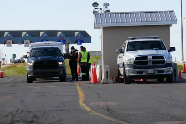 Health officials ask for documentation at the entry point on the P.E.I. side of Confederation Bridge. About 2,000 vehicles passed this way on Sunday, the first day vaccinated arrivals could come to the Island without having to isolate. (Jane Robertson/CBC - image credit)