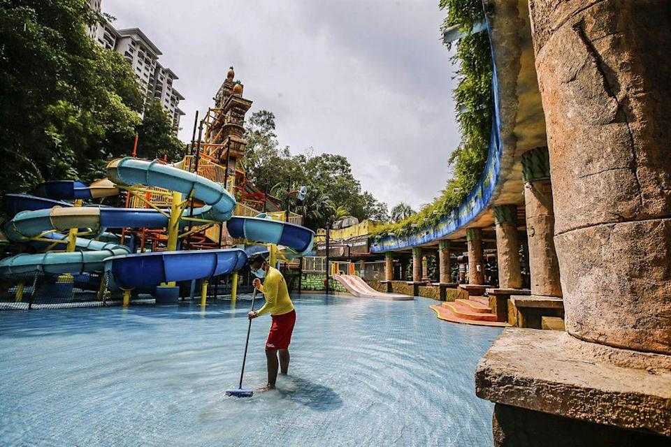 A worker is pictured getting the Sunway Lagoon theme park ready to reopen to visitors in Subang Jaya September 27, 2021. — Picture by Hari Anggara