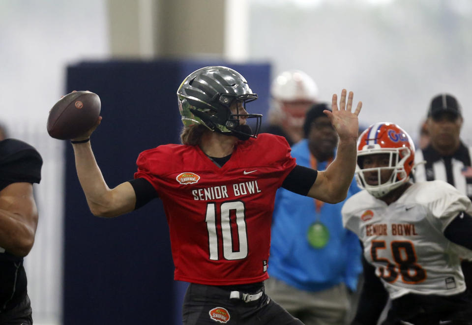Oregon's Justin Herbert throws a pass as the South squad practices for the Senior Bowl Thursday, Jan. 23, 2020, in Mobile, Ala. (AP Photo/Butch Dill)
