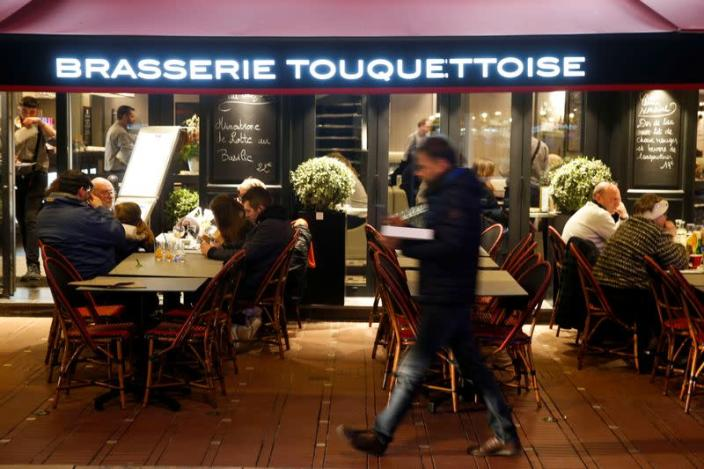 People enjoy dinner and drinks, after the French Prime Minister announcement that the shut down of no essentials commerces and places will start in France at midnight