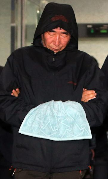 Lee Joon-seok the captain of the sunken ferry Sewol in the water off the southern coast, leaves a court which issued his arrest warrant in Mokpo, south of Seoul, South Korea, Saturday, April 19, 2014. The investigation into South Korea's ferry disaster focused on the sharp turn it took just before it began listing and on the possibility that a quicker evacuation order by the captain could have saved lives, officials said Friday, as rescuers struggled to find some 270 people still missing and feared dead. (AP Photo/Yonhap) KOREA OUT