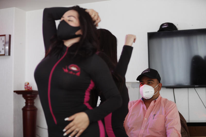Women wearing protective face masks amid the new coronavirus pandemic, dance in a client's home in Mexico City, Saturday, Aug. 8, 2020. The pandemic has forced business to adapt to a new normality and the adult entertainment industry is no exception. After three months of inactivity, Mi Ultimo Beso relaunched its table-dance-at-home service observing health measures. (AP Photo/Eduardo Verdugo)