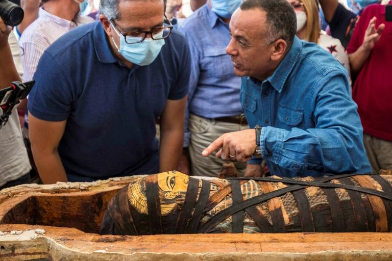 Opening one of the ornately decorated sarcophagi before assembled media, the team revealed mummified remains wrapped in burial cloth that bore hieroglyphic inscriptions in bright colours