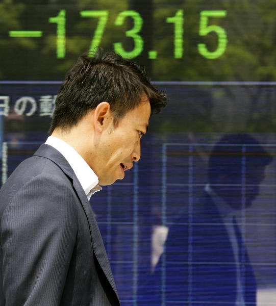 A man walks in front of the electronic board of a securities firm in Tokyo, Monday, June 4, 2012. Asia stock markets took a beating Monday as signs that the U.S. economic recovery might be shifting into reverse sent investors fleeing. Japan's Nikkei 224 index dropped 2 percent to 8,269.14. (AP Photo/Koji Sasahara)
