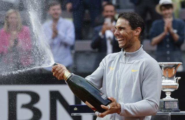FILE - In this May 20, 2018, file photo, Spain's Rafael Nadal sprays sparkling wine as he celebrates defeating Germany's Alexander Zverev in the final match of the Italian Open tennis tournament in Rome. Nadal is 79-2 for his career in the French Open, a .975 winning percentage. (AP Photo/Gregorio Borgia, File)