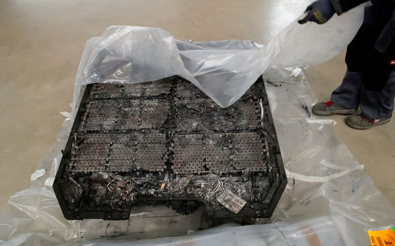 FILE PHOTO: A technician unpacks a completely burned Lithium-ion car battery before its dismantling by the German recycling firm Accurec in Krefeld