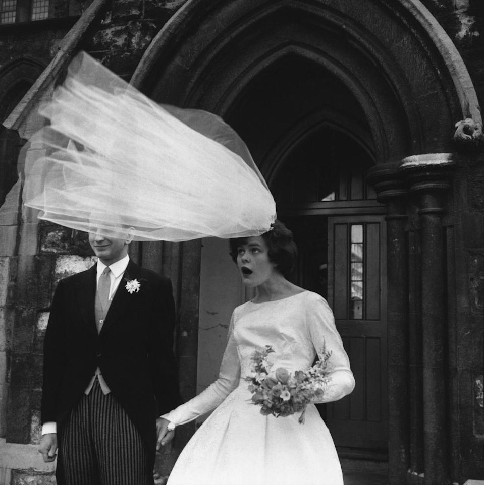 """<p>In the 1960s, hairstyles were almost like architectural creations that were constructed to last. Note that a strong breeze threatens to steal this bride's veil, but her hair stays firmly in place. (Sidenote: We love her graceful boatneck wedding dress.)</p><p><a href=""""http://www.goodhousekeeping.com/life/relationships/news/a39454/rollercoaster-wedding/"""" rel=""""nofollow noopener"""" target=""""_blank"""" data-ylk=""""slk:The story behind a hair-raising wedding »"""" class=""""link rapid-noclick-resp""""><em>The story behind a hair-raising wedding »</em></a></p>"""