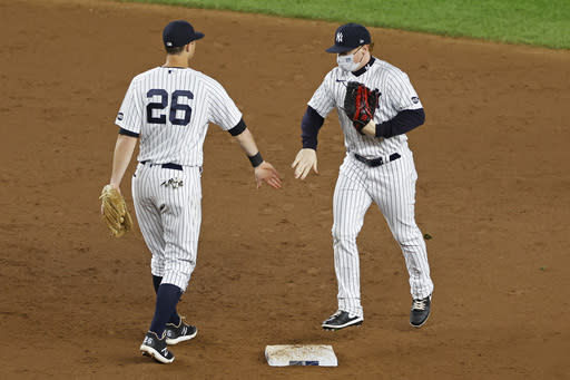 New York Yankees left fielder Clint Frazier, right, celebrates with DJ LeMahieu, left, after defeating the Toronto Blue Jays in a baseball game on Tuesday, Sept. 15, 2020, in New York. (AP Photo/Adam Hunger)