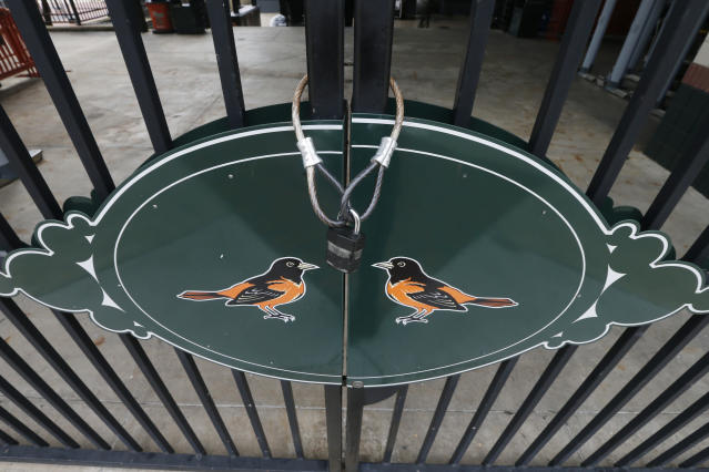 Locked gates and empty walkways are shown at Oriole Park at Camden Yards, home of the Baltimore Orioles baseball team, on what was to be opening day March 26, 2020, in Baltimore, Md. (AP Photo/Steve Helber)