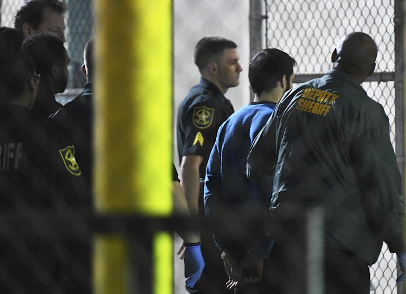 Esteban Santiago, 26, the suspect in the deadly shooting at Fort Lauderdale-Hollywood International Airport, is transported to the Broward County Main Jail by authorities, Saturday, Jan. 7, 2017. The gunman who fatally shot several people and wounded others on Friday in Fort Lauderdale's airport sent panicked passengers running out of the terminal and onto the tarmac with bags in hand. (Jim Rassol/South Florida Sun-Sentinel via AP)