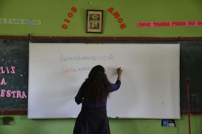 """Teacher Carmen Cazorla writes in the Quechua Indigenous language during a class on medicinal plants at a public primary school in Licapa, Peru, Wednesday, Sept. 1, 2021. """"For 500 years Spanish has been imposed in a way that reflects the racist and classist values of Peruvian society,"""" said Cazorla, an anthropologist who also teaches Quechua at the Catholic University of Peru. (AP Photo/Martin Mejia)"""