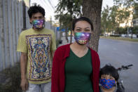 A family wear face masks with images of New Year celebrations in Bangkok, Thailand, Wednesday, Dec. 30, 2020. Officials in the Thai capital have announced new restrictions, including the closure of some entertainment facilities during the New Year's holiday, as infections continued to rise following a recent coronavirus outbreak. (AP Photo/Gemunu Amarasinghe)