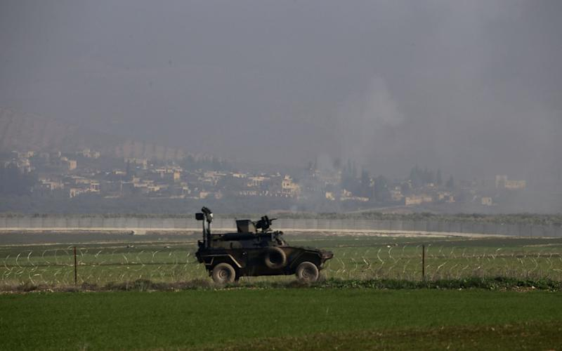 Smoke rises from PKK/PYD controlled Afrin's Nesreyieh district of Aleppo as Turkish Army's armoured vehicle deployed as reinforcement to troops at the border line - Anadolu