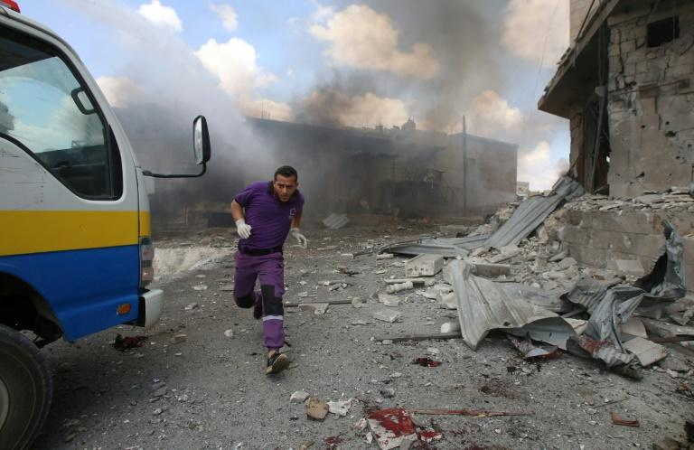 A rescuer from the Violet NGO runs during airstrikes by Syrian regime forces in Maar Shurin on the outskirts of Maarat al-Numan in northwest Syria on July 16, 2019