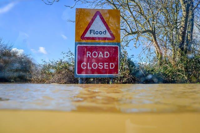 A road closed sign pokes out above floodwater and alerts motorists of flooding on the B4213 between Lower Apperlay and Tirley in Gloucestershire (Ben Birchall/PA)