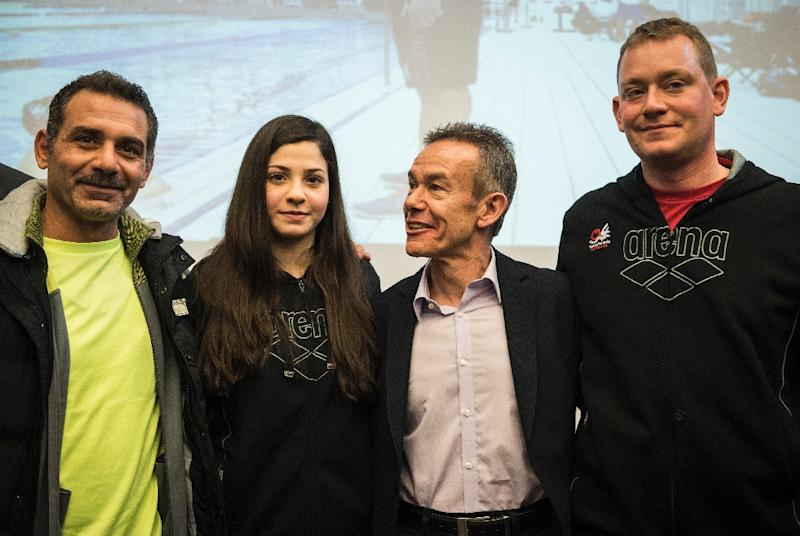 Syrian swimmer Yusra Mardini (2ndL), her father Izzat (L), coach Sven Spannekrebs (2ndR) and Pere Miro of the International Olympic Committee pose for a picture after a press conference in Berlin on March 18, 2016 (AFP Photo/Odd Andersen)