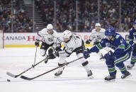 Los Angeles Kings' Alex Iafallo (19) reaches for the puck in front of Vancouver Canucks' Quinn Hughes (43) during the first period of an NHL hockey game Wednesday, Oct. 9, 2019, in Vancouver, British Columbia. (Darryl Dyck/The Canadian Press via AP)