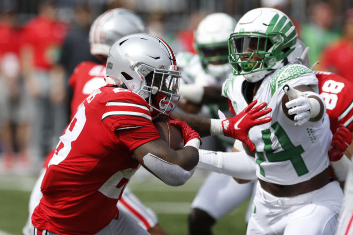 Ohio State running back Miyan Williams, left, tries to run past Oregon defensive lineman Bradyn Swinson during the first half of an NCAA college football game Saturday, Sept. 11, 2021, in Columbus, Ohio. Oregon beat Ohio State 35-28. (AP Photo/Jay LaPrete)