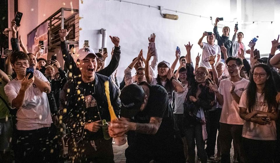 A pro-democracy supporter pops a bottle open during celebrations of the camp's unprecedented performance in the Sunday's district council elections. Photo: AFP