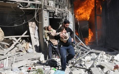 Men carry children as they run out of a burning building following a barrel bomb attack reportedly dropped by government forces in the northern Syrian city of Aleppo. - Credit: AFP