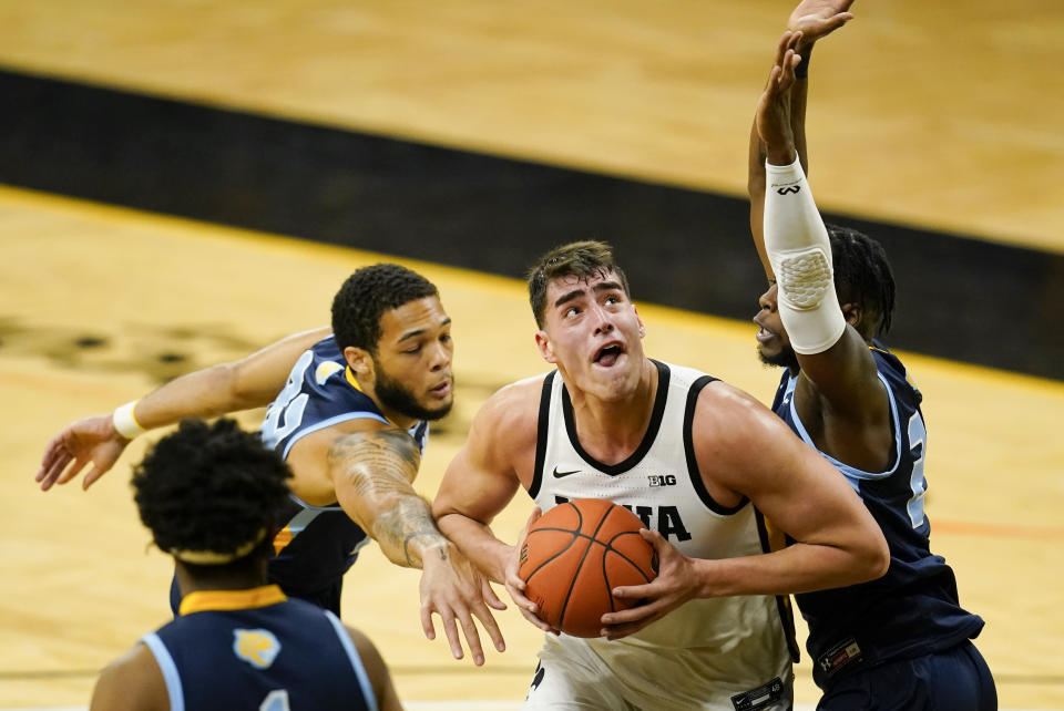 Iowa center Luka Garza, center, drives to the basket between Southern University's Andre Allen, left, and Samkelo Cele, right, during the first half of an NCAA college basketball game, Friday, Nov. 27, 2020, in Iowa City, Iowa. (AP Photo/Charlie Neibergall)