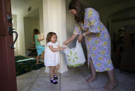 In this July 21, 2021 photo, Attorney Cynthia Carrasco White and her daughters, Charlotte, 6 and Mathilde, 3 receive a delivery by Instacart at their home front door in the Porter Ranch area of Los Angeles. Carrasco White, a single mother and a lawyer for a Los Angeles nonprofit, used to think delivery was a luxury she couldn't afford. But she started getting meals, groceries and other necessities delivered last year so she could avoid taking her young, unvaccinated daughters to the store. Carrasco White has come to see delivery as a lifeline that saves her time, gas money and child care expenses. She uses various apps, including Uber Eats and DoorDash, and takes advantage of deals when she can. (AP Photo/Damian Dovarganes)