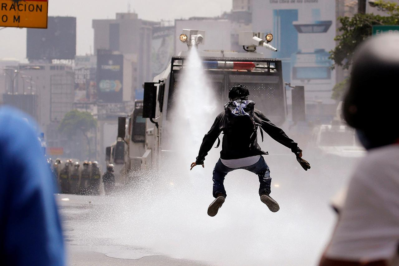 <p>A demonstrator jumps away from a jet of water released from a riot security forces vehicle during a rally against Venezuela's President Nicolas Maduro in Caracas, Venezuela, May 26, 2017. (Photo: Carlos Barria/Reuters) </p>
