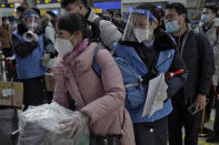 Workers wearing face masks and face shields to help curb the spread of the coronavirus assist masked passengers to board their trains at the South Train Station in Beijing, Thursday, Jan. 28, 2021. Efforts to dissuade Chinese from traveling for Lunar New Year appeared to be working. Beijing's main train station was largely quiet on the first day of the travel rush and estimates of passenger totals were smaller than in past years. (AP Photo/Andy Wong)