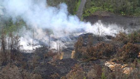 Molten rock flows and burst to the surface, threatening homes in a rural area in this still image from an aerial video taken from a Hawaii Army National Guard a week after the eruption of the Kilauea volcano, in Pahoa, Hawaii, U.S., May 10, 2018. Courtesy Andrew Jackson/Hawaii DoD/Handout via REUTERS