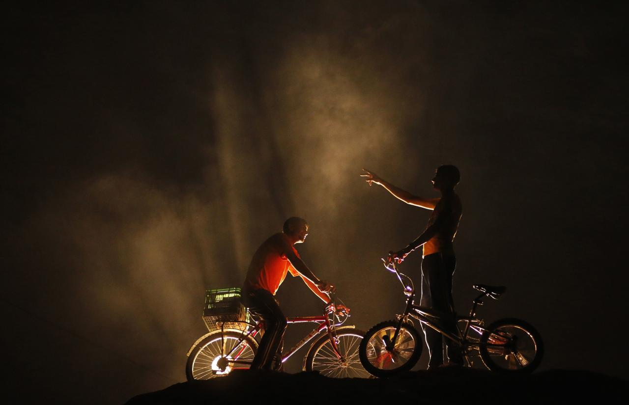 Palestinian boys stand with their bicycles on top of a sandhill, lit by streetlamps behind, near the beach in the northern Gaza Strip September 19, 2013. REUTERS/Mohammed Salem (GAZA - Tags: SOCIETY TPX IMAGES OF THE DAY)