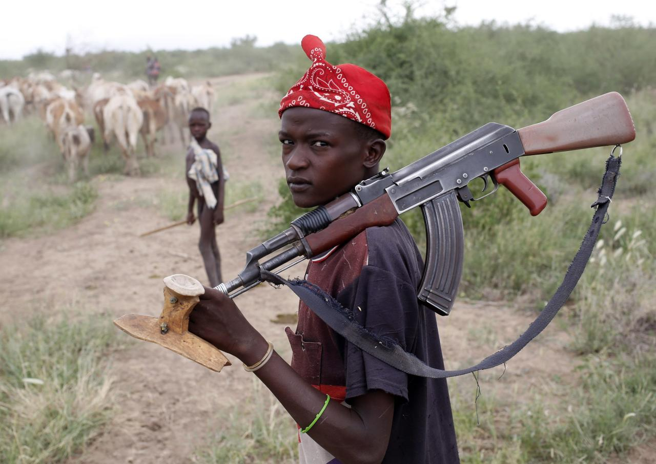A Turkana boy herds cows as he carries a rifle in north western Kenya near the town of Kibish inside the Turkana region of the Ilemy Triangle September 26, 2014. The Ilemi Triangle is a disputed region in East Africa, claimed by South Sudan and Kenya, and bordering Ethiopia. The dispute arose from unclear wording of a 1914 treaty which tried to allow free movement of the Turkana people, nomadic herders who had traditionally grazed the area. REUTERS/Goran Tomasevic (KENYA - Tags: SOCIETY POLITICS)
