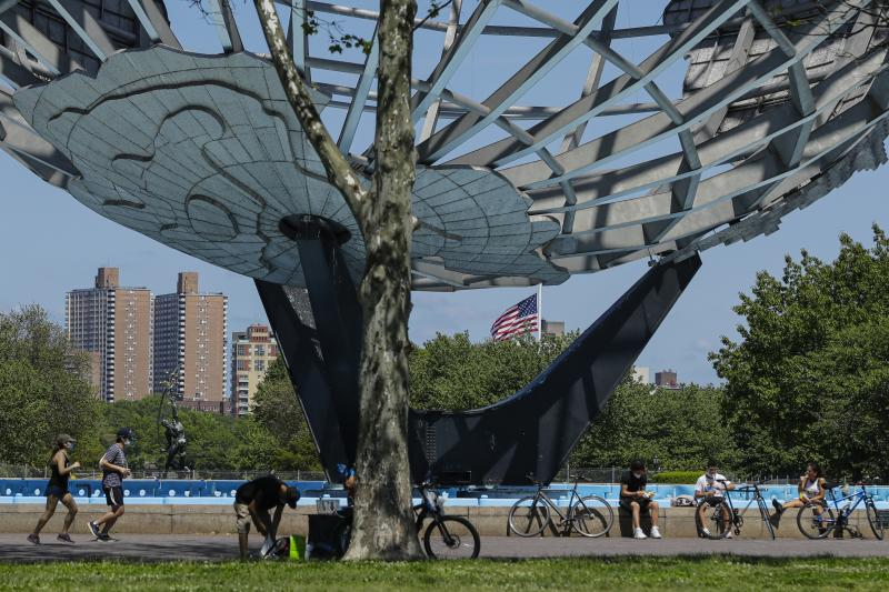 Runners and cyclists wear protective masks during the coronavirus pandemic as they pass the Unisphere, Tuesday, May 26, 2020, in the Queens borough of New York. (AP Photo/Frank Franklin II)
