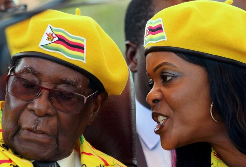 FILE PHOTO: President Robert Mugabe listens to his wife Grace Mugabe at a rally of his ruling ZANU-PF party in Harare