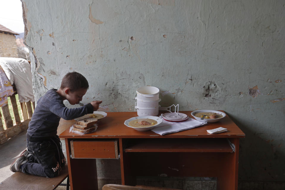 Milan Bastyur, a 4 year old Hungarian Roma child, eats lunch outside his family's home in Bodvaszilas, Hungary, Monday, April 12,2021. Many students from Hungary's Roma minority do not have access to computers or the internet and are struggling to keep up with online education during the pandemic. Surveys show that less than half of Roma families in Hungary have cable and mobile internet and 13% have no internet at all. (AP Photo/Laszlo Balogh)