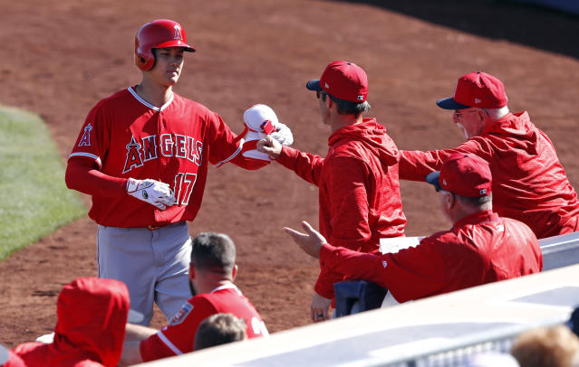 Los Angeles Angels' Shohei Ohtani (17) is greeted by teammates after hitting a single during the fifth inning of a spring training baseball game against the San Diego Padres, Monday, Feb. 26, 2018, in Peoria, Ariz. (AP Photo/Charlie Neibergall)