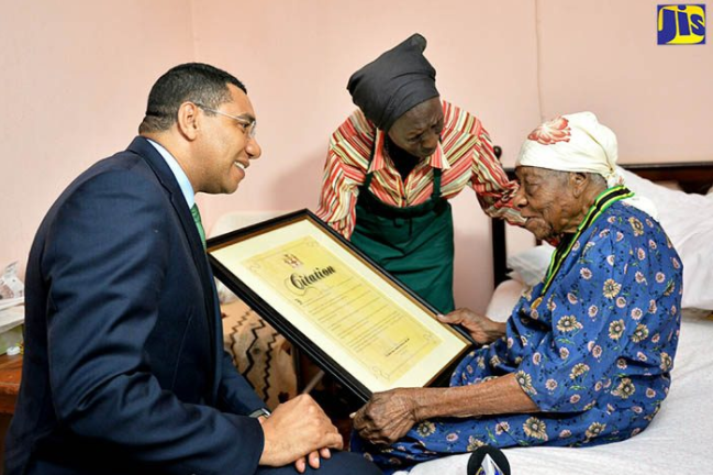 Violet Mosse-Brown was known as Aunt V. Prime Minister Andrew Holness gave her the Prime Minister's Medal of Appreciation in April at her home, with her caretaker. (Jamaican Information Service)