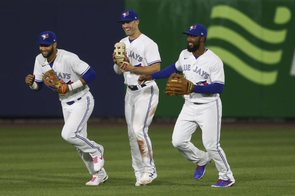 Toronto Blue Jays' Lourdes Gurriel Jr., left, Randal Grichuk, center, and Teoscar Hernandez, right celebrate the Toronto Blue Jays' 9-0 win over the Baltimore Orioles after the baseball game in Buffalo, N.Y., Thursday, June 24, 2021. (AP Photo/Joshua Bessex)