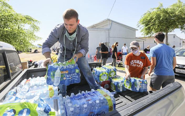 "Volunteer Holden Yorgason helps load water donations for fire victims at the Calipatria Unified School District offices on Tuesday. <span class=""copyright"">(Eduardo Contreras / San Diego Union-Tribune)</span>"