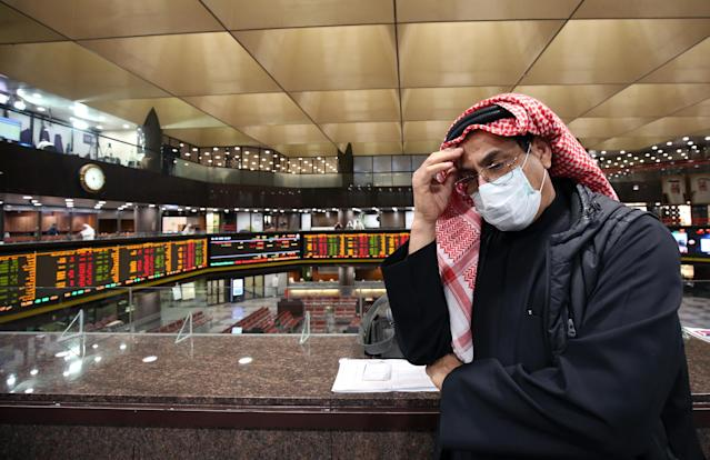 A Kuwaiti trader wearing a protective mask follows the market at the Boursa Kuwait stock exchange in Kuwait City on 1 March. (Yasser Al-Zayyat/AFP via Getty)