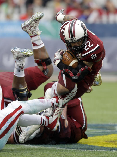 South Carolina running back Brandon Wilds (22) dives for a short gain as he is tripped up by the Wisconsin defense during the first half of the Capital One Bowl NCAA college football game in Orlando, Fla., Wednesday, Jan. 1, 2014.(AP Photo/John Raoux)