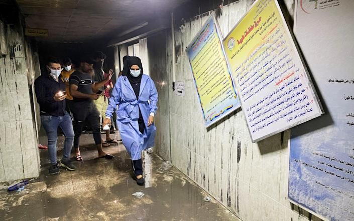 People and medical staff members walk at Ibn Khatib hospital after the fire - Reuters