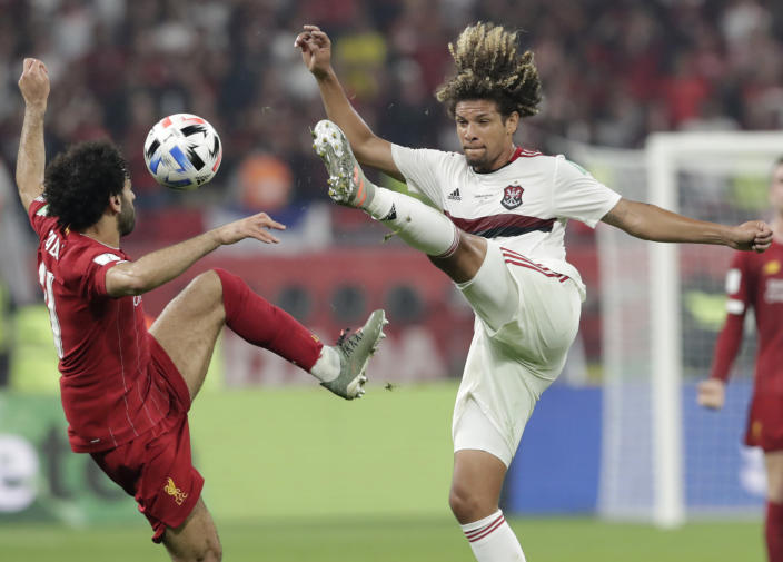 Flamengo's Willian Arao, right, challenges Liverpool's Mohamed Salah, left, during the Club World Cup final soccer match between Liverpool and Flamengo at Khalifa International Stadium in Doha, Qatar, Saturday, Dec. 21, 2019. (AP Photo/Hassan Ammar)