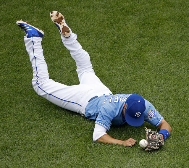 Kansas City Royals second baseman Whit Merrifield struggles to field a single hit by New York Yankees' Ronald Torreyes during the eighth inning of a baseball game Sunday, May 20, 2018, in Kansas City, Mo. (AP Photo/Charlie Riedel)