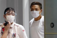 Pyae Lyan Aung, right, a member of the Myanmar national team who raised a three-finger salute during a qualifying match for the 2022 World Cup in late May, arrives at Kansai International Airport in Osaka Prefecture, Japan on Thursday June 17, 2021. Pyae Lyan Aung has refused to return home and is seeking asylum, a request the government was considering taking into account unrest in his country following a coup. (Kyodo News via AP)