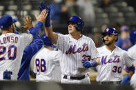 New York Mets' James McCann (33) celebrates with teammates after hitting a two-run home run during the eighth inning of a baseball game against the Philadelphia Phillies Wednesday, April 14, 2021, in New York. (AP Photo/Frank Franklin II)