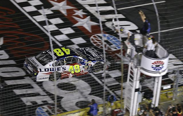 Driver Jimmie Johnson (48) takes the checkered flag to win the NASCAR Sprint Cup series Coca-Cola 600 auto race at the Charlotte Motor Speedway in Concord, N.C., Sunday, May 25, 2014. (AP Photo/Gerry Broome)