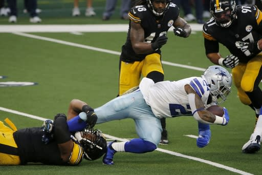 Dallas Cowboys running back Ezekiel Elliott (21) is stopped behind the line of scrimmage by Pittsburgh Steelers defensive end Stephon Tuitt, bottom left, as Bud Dupree (48) and Cameron Heyward (97) look on in the first half of an NFL football game in Arlington, Texas, Sunday, Nov. 8, 2020. (AP Photo/Michael Ainsworth)